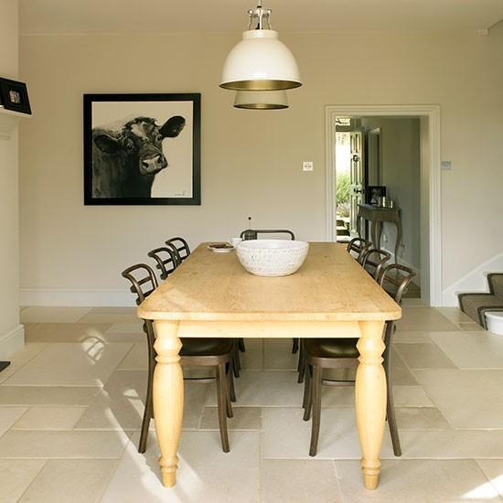 Vidiecka jedáleň s elegantnými prvkami, kvalitnou kamennou dlažbou a nápaditým obrazom na stene.