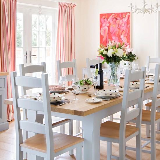 Biela jedáleň s oranžovými a ružovými akcentami.