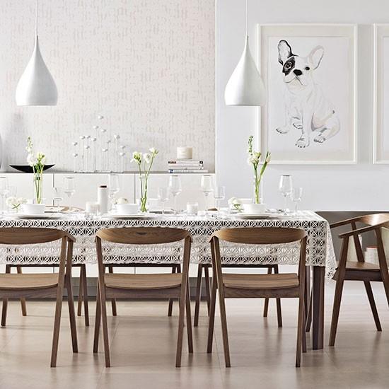 Biela jedáleň s dominantným orechovým nábytkom.